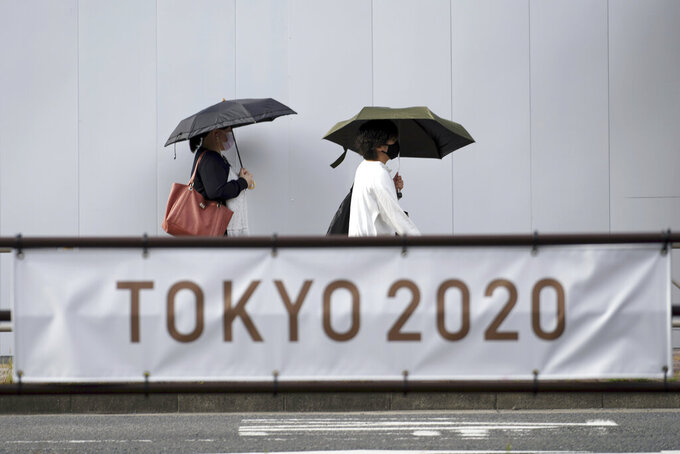 People wearing masks to help protect against the spread of the coronavirus walk near a banner to promote the Tokyo Olympic Games Tuesday, May 25, 2021, in Tokyo. (AP Photo/Eugene Hoshiko)