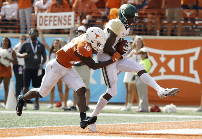 Baylor wide receiver Denzel Mims (15) makes a 19-yard catch in front of Texas defensive back Davante Davis (18) for a touchdown during the first half of an NCAA college football game, Saturday, Oct. 13, 2018, in Austin, Texas. (AP Photo/Eric Gay)