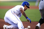 Kansas City Royals' Adalberto Mondesi slides into third base as the ball gets past Chicago White Sox third baseman Yoan Moncada, right, during the first inning of a baseball game at Kauffman Stadium in Kansas City, Mo., Tuesday, July 16, 2019. Mondesi scored on the play. Moncada was charged with an error. (AP Photo/Orlin Wagner)