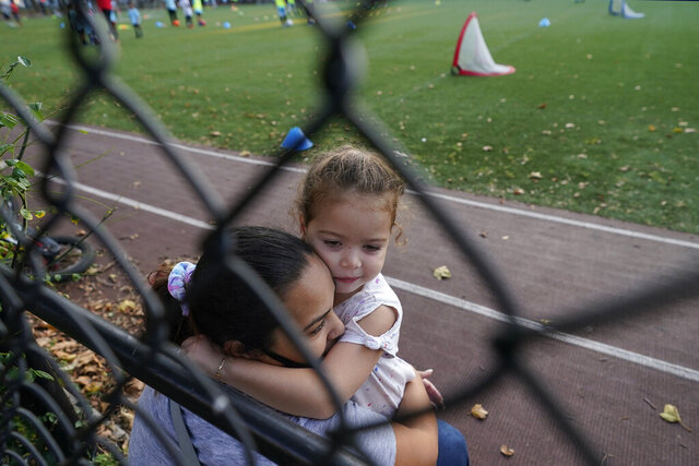 A woman embraces her young daughter as they spend time outdoors at a public park in the Gravesend section of Brooklyn, Monday, Sept. 28, 2020, in New York. The neighborhood has seen a recent uptick in COVID-19 cases. New York Gov. Andrew Cuomo raised alarms Monday about the emergence of a handful of coronavirus hot spots in New York, including the Gravesend neighborhood, saying just 10 ZIP codes represented more than a quarter of the state's new infections in recent testing. (AP Photo/Kathy Willens)