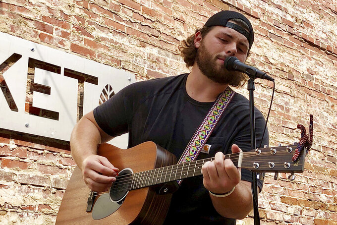 Marshall football player Will Ulmer sings and plays guitar July 18, 2021, in Huntington, W.Va. The NCAA's decision last month to lift its longtime ban on an athlete being compensated for their name, image and likeness has opened up Ulmer and others to show off their artistic sides. (AP Photo/John Raby)