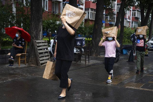 Residents wearing face masks to curb the spread of the coronavirus hold up paper bags to protect against the rain in Beijing on Thursday, June 18, 2020. A new coronavirus outbreak in Beijing saw a decline in daily cases Thursday while the United States increased pressure on China's leaders to reveal what they know about the pandemic. (AP Photo/Ng Han Guan)