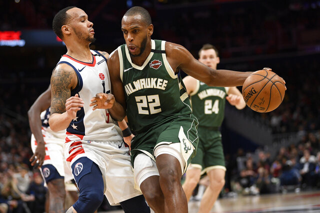 Milwaukee Bucks forward Khris Middleton (22) dribbles against Washington Wizards guard Shabazz Napier (5) during the first half of an NBA basketball game, Monday, Feb. 24, 2020, in Washington. (AP Photo/Nick Wass)