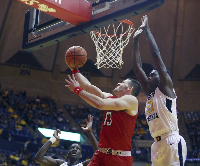 Texas Tech guard Matt Mooney (13) drives to the basket while defended by West Virginia forward Wesley Harris (21) during the first half of an NCAA college basketball game Wednesday, Jan. 2, 2019, in Morgantown, W.Va. (AP Photo/Raymond Thompson)