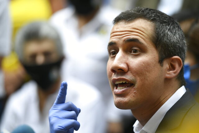 FILE - In this June 17, 2020 file photo, Venezuelan opposition leader Juan Guaido speaks upon his arrival to the headquarters of Democratic Action political party in Caracas, Venezuela, the day after Venezuela's Supreme Court ordered its takeover ahead of parliamentary elections expected this year. A coalition of political parties in Venezuela led by U.S.-backed Juan Guaido said Sunday, Aug. 2, that it won't participate in upcoming congressional elections called by officials loyal to President Nicolas Maduro.  (AP Photo/Matias Delacroix, File)
