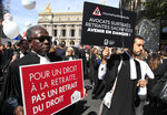 Lawyers march with placards during a protest against the planned pension change in Paris, Monday, Sept. 16, 2019. French lawyers, doctors, nurses, pilots and others are taking to the streets of Paris to protest planned pension changes by French President Emmanuel Macron's government. Placards read,