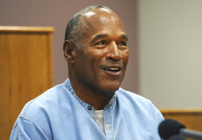 FILE - In this July 20, 2017, file photo, former NFL football star O.J. Simpson appears via video for his parole hearing at the Lovelock Correctional Center in Lovelock, Nev. Simpson and a Las Vegas hotel-casino have settled a lawsuit alleging that unnamed employees defamed Simpson by telling a celebrity news site he had been banned from the property in November 2017 for being drunk and disruptive. Simpson's attorney declined comment about the agreement. (Jason Bean/The Reno Gazette-Journal via AP, Pool, File)