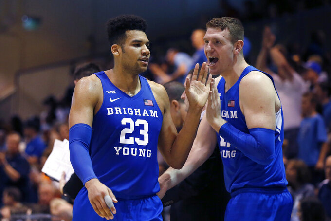 BYU forward Yoeli Childs (23) is greeted by Kolby Lee as he walks off the court during the second half of the team's NCAA college basketball game against Pepperdine on Saturday, Feb. 29, 2020, in Malibu, Calif. (AP Photo/Ringo H.W. Chiu)