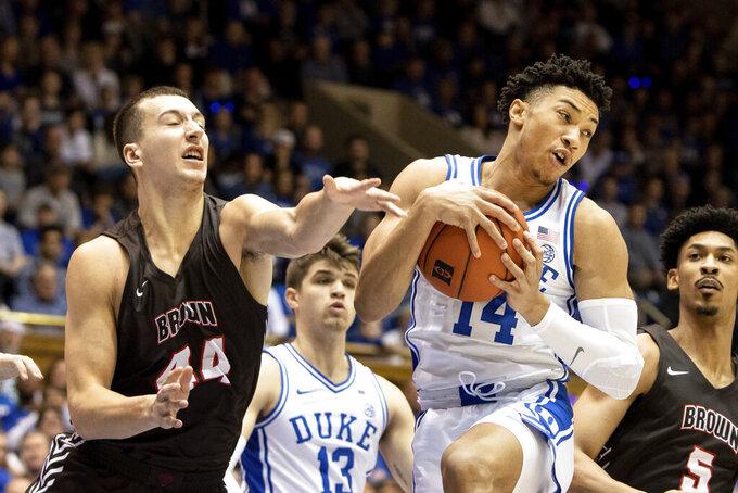 Duke's Jordan Goldwire (14) gathers a rebound ahead of Brown's Matt DeWolf (44) during the first half of an NCAA college basketball game in Durham, N.C., Saturday, Dec. 28, 2019. (AP Photo/Ben McKeown)