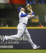 Milwaukee Brewers' Mike Moustakas makes a running catch on a ball hit by Cincinnati Reds' Yasiel Puig during the second inning of a baseball game Friday, June 21, 2019, in Milwaukee. (AP Photo/Morry Gash)
