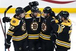 Boston Bruins' Craig Smith (12) celebrates his hat-trick goal with teammates Charlie McAvoy (73), David Krejci (46) and Taylor Hall (71) during the third period of an NHL hockey game against the Buffalo Sabres, Saturday, May 1, 2021, in Boston. (AP Photo/Michael Dwyer)