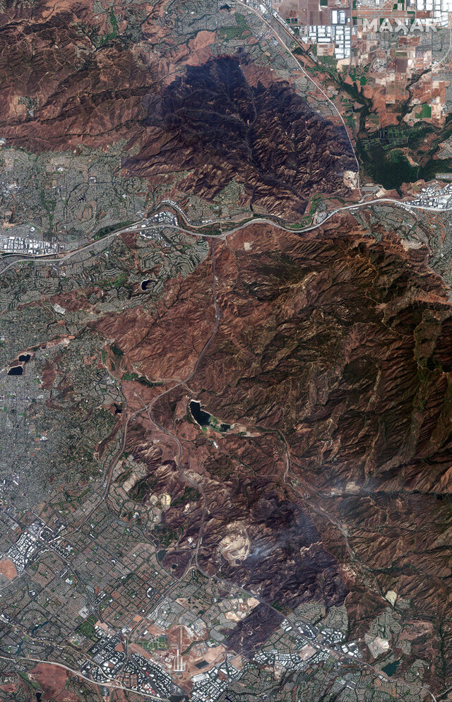 This satellite image provided by Maxar Technologies, shows the burned out mountains from the Blue Ridge Fire near homes in Yorba Linda, Calif., Wednesday, Oct. 28, 2020. Thousands of Californians were allowed to return to their homes Wednesday as calmer winds helped firefighters beat back two wind-driven wildfires that had spurred widespread evacuations. (Maxar Technologies via AP)