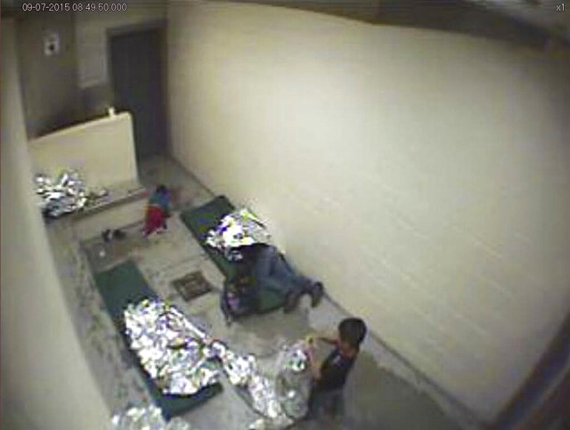 FILE - This September, 2015, file image made from U.S. Border Patrol surveillance video shows a child crawling on the concrete floor near the bathroom area of a holding cell, and a woman and children wrapped in Mylar sheets at a U.S. Customs and Border Protection station in Douglas, Ariz. A U.S. judge in Arizona has issued a permanent order requiring the Border Patrol to provide clean mats and thin blankets to migrants within 12 hours of arriving at a facility. The order issued on Wednesday, Feb. 19, 2020, applies to eight Border Patrol stations in Arizona following a lawsuit that claims the agency holds migrants in overcrowded, unsafe and inhumane conditions. (U.S. Border Patrol via AP, File)