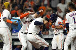 Houston Astros' Jose Altuve (27) celebrates with teammates after hitting a game-winning grand slam during the 10th inning of a baseball game against the Texas Rangers Tuesday, June 15, 2021, in Houston. The Astros won 6-3. (AP Photo/David J. Phillip)