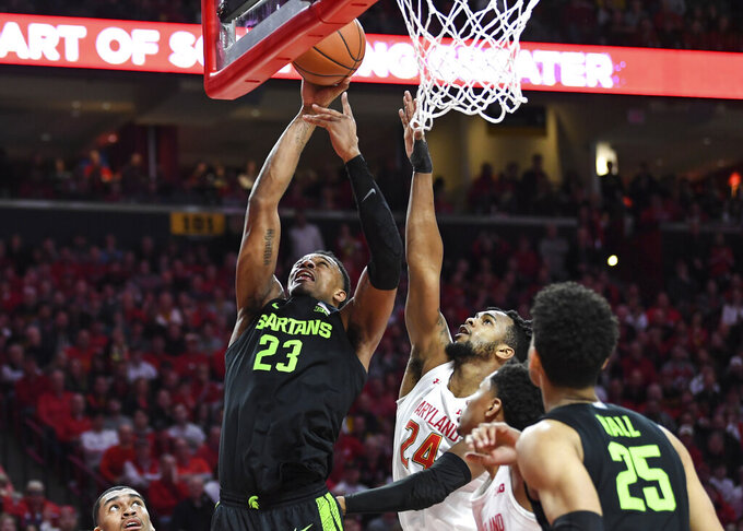 Michigan State forward Xavier Tillman Sr. (23) goes to the basket for a layup against Maryland forward Donta Scott (24) during the first half of an NCAA college basketball game Saturday, Feb. 29, 2020, in College Park, Md. (AP Photo/Terrance Williams)
