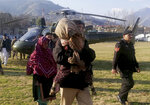 A volunteer carries a girl who was injured in an avalanche, at a helipad in Muzaffarabad, the capital of Pakistan-administered Kashmir, Tuesday, Jan. 14, 2020. Severe winter weather has claimed more lives as avalanches triggered by heavy snowfall killed more than 50 people in Pakistan-administered Kashmir while a dozen died in neighboring Afghanistan, officials said Tuesday. (AP Photo/M.D. Mughal)