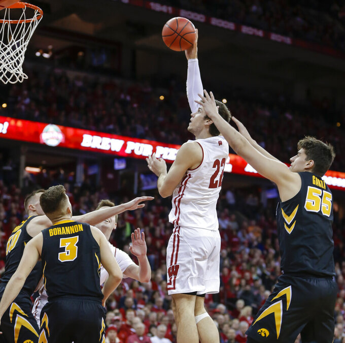Wisconsin's Ethan Happ (22) shoots between Iowa's Jordan Bohannon (3) and Luka Garza (55) during the second half of an NCAA college basketball game Thursday, March 7, 2019, in Madison, Wis. Wisconsin won 65-45. (AP Photo/Andy Manis)