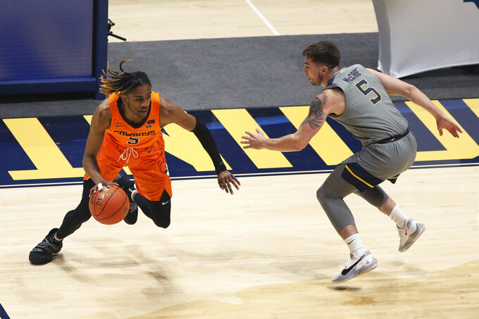 Oklahoma State guard Rondel Walker (5) is defended by West Virginia guard Jordan McCabe (5) during the first half of an NCAA college basketball game Saturday, March 6, 2021, in Morgantown, W.Va. (AP Photo/Kathleen Batten)