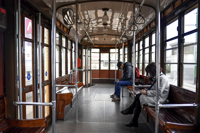 People wear sanitary masks as they ride an empty tram in downtown Milan, Italy, Wednesday, Feb. 26, 2020. Italy has been struggling to contain the rapidly spreading outbreak that has given the country more coronavirus cases outside Asia than anywhere else. (Claudio Furlan/LaPresse via AP)