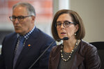 Oregon Gov. Kate Brown, with Washington Gov. Jay Inslee, right, listens to a question from the media during an event to sign a memorandum of intent to replace the Interstate 5 bridge in Vancouver, Wash., Monday, Nov. 18, 2019. (Nathan Howard/The Columbian via AP)