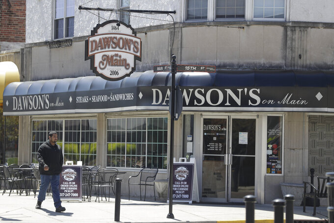 A man walks past Dawson's on Main, Tuesday, April 21, 2020, in Indianapolis. A.J. Foyt came to Indianapolis in 1958 a fearless rookie who rented a basement for $15 per week and slept on a cot not too far from the roar of the cars and crowds at Indianapolis Motor Speedway. Sometimes, he would walk to Main Street and join other drivers for breakfast at a drug store. That drug store where Foyt used to eat is still a restaurant, Dawson's on Main. The speedway is closed due to the coronavirus pandemic. (AP Photo/Darron Cummings)