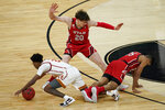 Southern California's Tahj Eaddy, left, and Utah's Alfonso Plummer, right, fall in front of Mikael Jantunen (20) during the first half of an NCAA college basketball game in the quarterfinal round of the Pac-12 men's tournament Thursday, March 11, 2021, in Las Vegas. (AP Photo/John Locher)
