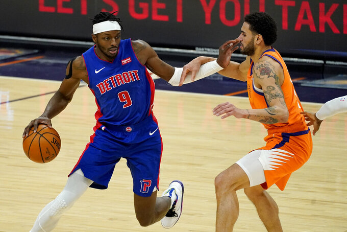 Detroit Pistons forward Jerami Grant (9) drives against Phoenix Suns forward Abdel Nader during the first half of an NBA basketball game, Friday, Feb. 5, 2021, in Phoenix. (AP Photo/Matt York)