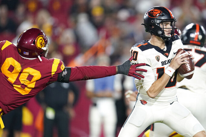 Oregon State quarterback Chance Nolan, right, is pressured by Southern California linebacker Drake Jackson (99) during the first half of an NCAA college football game Saturday, Sept. 25, 2021, in Los Angeles. (AP Photo/Marcio Jose Sanchez)