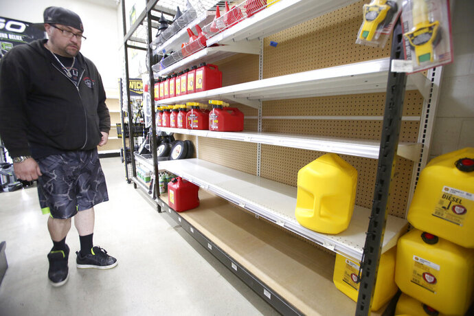 Grass Valley's Dionicio Torres looks at the gas can selection before taking the last 5-gallon gas can on the shelves at B&C Ace Home & Garden Center, in Grass Valley, Calif., Tuesday, Nov. 19, 2019, in preparation of Wednesday's planned public safety power shutdown. (Elias Funez/The Union via AP)