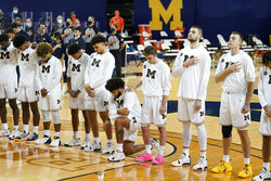 Michigan forward Isaiah Livers kneels during the national anthem before an NCAA college basketball game against Bowling Green, Wednesday, Nov. 25, 2020, in Ann Arbor, Mich. (AP Photo/Carlos Osorio)