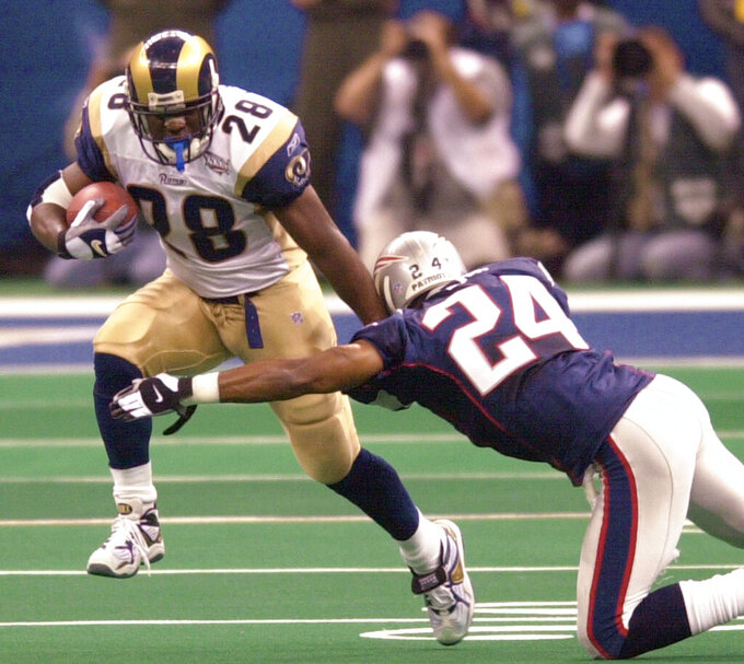 File-This Feb. 3, 2002, file photo shows St. Louis Rams running back Marshall Faulk (28) fending of New England Patriots cornerback Ty Law (24) during first-quarter play of Super Bowl XXXVI in New Orleans. The Greatest Show On Turf. When the St. Louis Rams were partying like it was 1999, they scored 526 points; ranked first in yards, yards passing, and TD passes; and were second in yards rushing per attempt. Faulk rushed for 1,381 yards and seven touchdowns, caught 87 balls for 1,087 yards, with five more TDs, and was the NFL Offensive Player of the Year for the first of three straight seasons. (AP Photo/Tony Gutierrez, File)