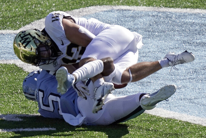 North Carolina defensive back Patrice Rene (5) tackles Wake Forest wide receiver Nolan Groulx (13) during the first half of an NCAA college football game in Chapel Hill, N.C., Saturday, Nov. 14, 2020. (AP Photo/Gerry Broome)