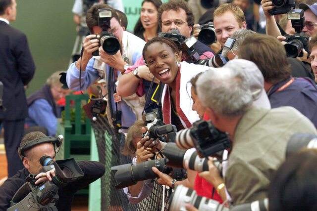 FILE - In this June 8, 2002, file photo, Venus Williams, surrounded by reporters, smiles after she made a picture of her sister Serena after the women's final of the French Open tennis tournament at Roland Garros stadium in Paris. Serena defeated her sister Venus 7-5, 6-3. (AP Photo/Francois Mori, File)