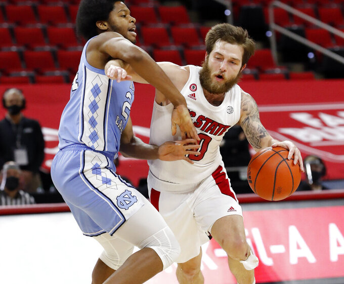North Carolina State's Braxton Beverly (10) tries to drive around North Carolina's Kerwin Walton (24) during the first half of an NCAA college basketball game in Raleigh, N.C., Tuesday, Dec. 22, 2020 (Ethan Hyman/The News & Observer via AP)