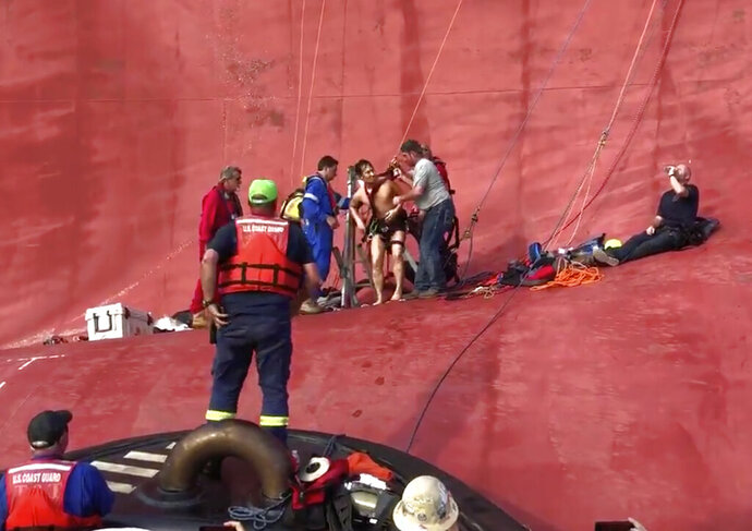 In this image taken from U.S. Coast Guard video on Monday, Sept. 9, 2019, a crew member of a capsized cargo ship is pulled from the vessel by Coast Guard rescuers off Jekyll Island, Ga. Coast Guard rescuers pulled four trapped men alive from the ship Monday, drilling into the hull's steel plates to extract the crew members more than a day after their vessel overturned while leaving a Georgia port. (U.S. Coast Guard via AP)