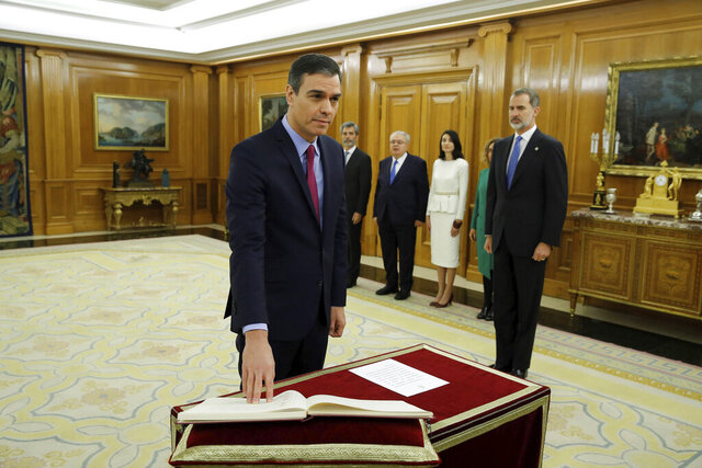 Spanish Socialist leader Pedro Sanchez takes his oath of office during the swearing in ceremony watched by Spains King Felipe VI, right at the Zarzuela Palace just outside of Madrid, Spain, Wednesday Jan. 8, 2020. Sanchez has taken an oath as Spanish prime minister a day after his proposal to form a leftist coalition government narrowly won a parliamentary confidence vote with support from smaller parties. (Juan Carlos Hidalgo/Pool Photo via AP)