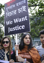 Protesters hold placards and gather to demand justice for an 18-year-old woman who was killed after she was set on fire for refusing to drop sexual harassment charges against her Islamic school's principal, in Dhaka, Bangladesh, Friday, April 19, 2019. Nusrat Jahan Rafi told her family she was lured to the roof of her rural school in the town of Feni on April 6 and asked to withdraw the charges by five people clad in burqas. When she refused, she said her hands were tied and she was doused in kerosene and set alight. Rafi told the story to her brother in an ambulance on the way to the hospital and he recorded her testimony on his mobile phone. She died four days later in a Dhaka hospital with burns covering 80% of her body. (AP Photo/Mahmud Hossain Opu)