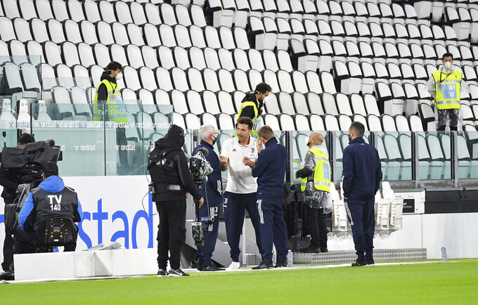 Juventus goalie Gianluigi Buffon, centre, stands on the pitch of the Allianz Stadium in Turin, Italy, Sunday, Oct. 4, 2020 ahead of the scheduled Serie A soccer match between Juventus and Napoli. Napoli is likely to be handed a 3-0 loss by the Italian league's judge for failing to show for its Serie A match at Juventus on Sunday night. Napoli did not travel to Turin for the match after local health authorities ordered the squad into quarantine after two players tested positive for the coronavirus. (Tano Pecoraro/LaPresse via AP)