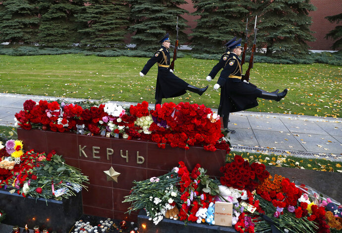 The Kremlin guards march past candles and flowers placed in memory of the victims of Wednesday's attack on a vocational college in Kerch, Crimea, at the memorial stone with the word Kerch in the Alexander Garden near the Kremlin, Moscow, Russia, Thursday, Oct. 18, 2018. A top official in Crimea says authorities are searching for a possible accomplice of the student whose shooting-and-bomb attack on his vocational school killed 20 people and wounded more than 50 others. (AP Photo/Pavel Golovkin)