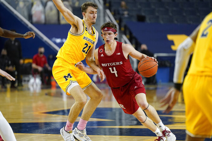 Rutgers guard Paul Mulcahy (4) drives on Michigan Wolverines guard Franz Wagner (21) in the first half of an NCAA college basketball game in Ann Arbor, Mich., Thursday, Feb. 18, 2021. (AP Photo/Paul Sancya)