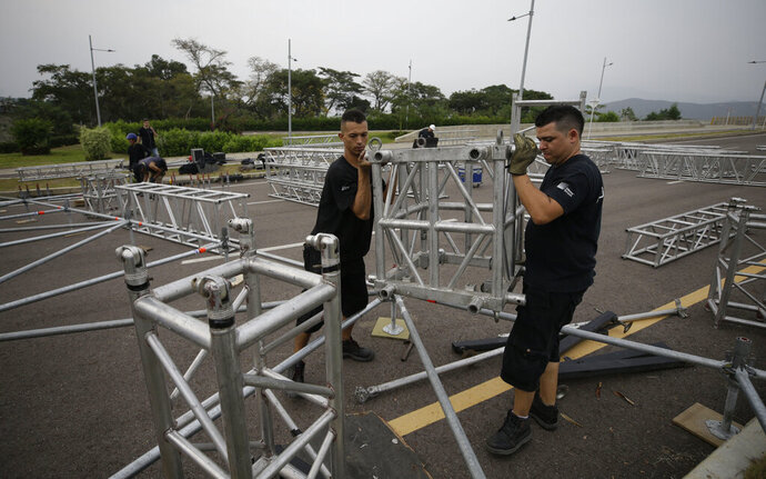 Workers build the stage for an upcoming concert coined: