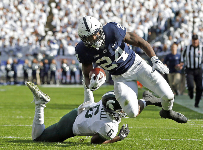 Penn State's Miles Sanders (24) is tripped by Michigan State's David Dowell (6) after a long run during the first half of an NCAA college football game in State College, Pa., Saturday, Oct. 13, 2018. (AP Photo/Chris Knight)