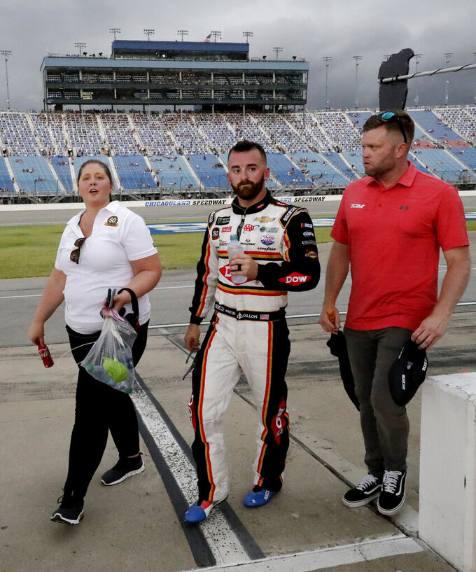 Austin Dillon, center, walks with his crew during a rain delay during the NASCAR Cup Series auto race at Chicagoland Speedway in Joliet, Ill., Sunday, June 30, 2019. (AP Photo/Nam Y. Huh)