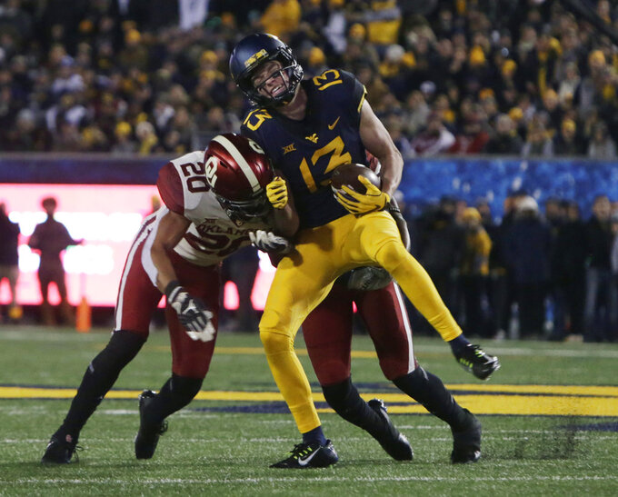 West Virginia wide receiver David Sills V (13) is tackled by Oklahoma safety Robert Barnes (20) during the first half of an NCAA college football game Friday, Nov. 23, 2018, in Morgantown, W.Va. (AP Photo/Raymond Thompson)