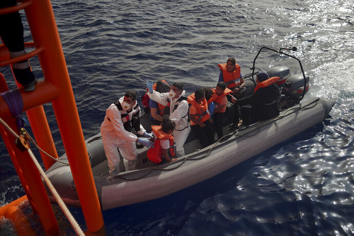 Members of the Maltese Armed Forces help migrant children disembark from the Ocean Viking and board their rescue boat in the Mediterranean Sea, Friday, Sept. 20, 2019. Malta has agreed to take in 35 migrants fleeing Libya who were rescued by the humanitarian ship a day earlier. (AP Photo/Renata Brito)