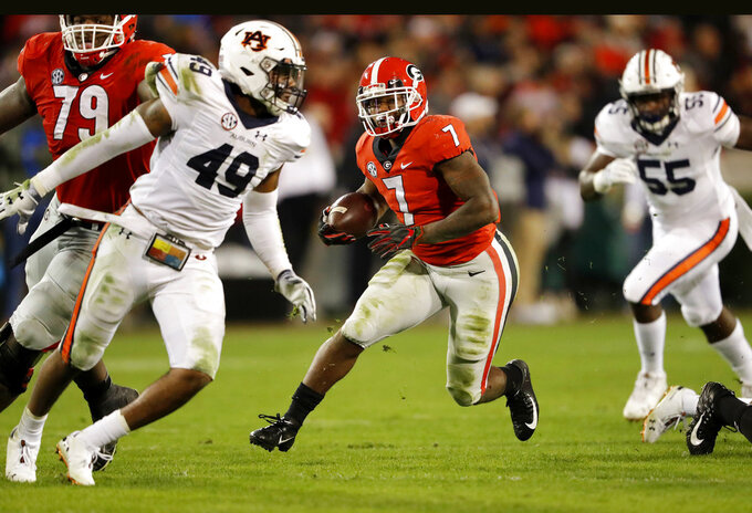 Georgia running back D'Andre Swift (7) looks for running room against Auburn defenders Darrell Williams (49) and T.D. Moultry (55) during the second half of an NCAA college football game Saturday, Nov. 10, 2018, in Athens, Ga.  (AP Photo/John Bazemore)
