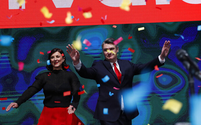 Zoran Milanovic, the liberal opposition candidate, right, waves to supporters his headquarters claimed victory in a presidential elections in Zagreb, Croatia, Sunday, Jan. 5, 2020. The exit poll carried by public broadcaster HRT and conducted by the IPSOS polling agency says Zoran Milanovic won 53% of votes while Kolinda Grabar Kitarovic garnered nearly 47%. If confirmed in the official vote tally, the result would mean a blow for the ruling conservatives while Croatia holds the European Union's rotating presidency, and before a parliamentary election later this year. (AP Photo/Darko Bandic)