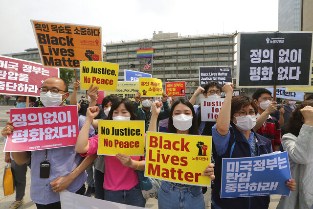 South Korean protesters shout slogans during a protest over the death of George Floyd, a black man who died after being restrained by Minneapolis police officers on May 25, near the U.S. embassy in Seoul, South Korea, Friday, June 5, 2020. The signs read