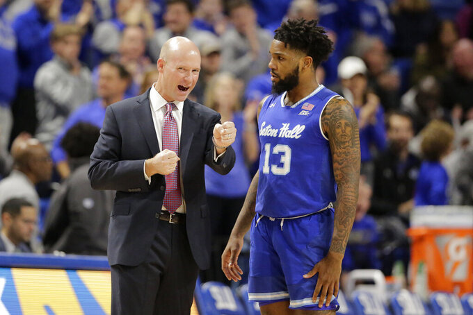 FILE - In this Nov. 17, 2019, file photo, Seton Hall head coach Kevin Willard, left, talks with guard Myles Powell (13) during the first half of an NCAA college basketball game against Saint Louis in St. Louis. Powell has sued Seton Hall, coach Kevin Willard and a staff member for failing to diagnose a knee injury during his senior season, causing him to suffer severe physical and financial damage. (AP Photo/Jeff Roberson, File)