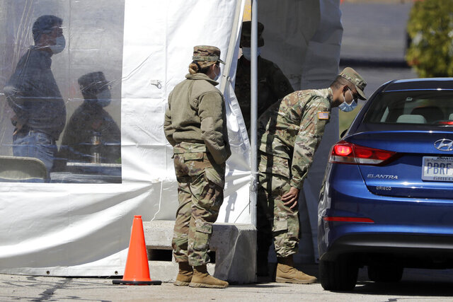 A member of the Rhode Island National Guard, center right, greets a visitor in a vehicle at a coronavirus testing site, Monday, April 6, 2020, at Twin River Casino, in Lincoln, R.I.  Gov. Gina Raimondo announced Monday that CVS Health is rolling out a free, rapid COVID-19 test at the new drive-through testing site. Results from tests being administered at the site could be ready in as little as 15 minutes, the governor said. (AP Photo/Steven Senne)